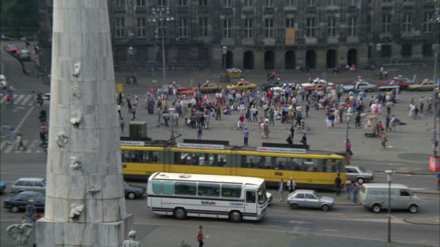 pull back from crowd of people to dam square with the national monument, a white stone pillar and the royal palace with cupola. plaza or town square. cars driving on city street. landmarks. europe. - 1985 bildbanksvideor och videomaterial från bakom kulisserna