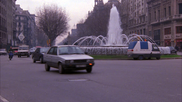 stockvideo's en b-roll-footage met wide angle of cars driving on city street, roundabout around a fountain. multi-story building, could be apartment buildings, hotels, office buildings on both sides of street. barcelona. - 1992