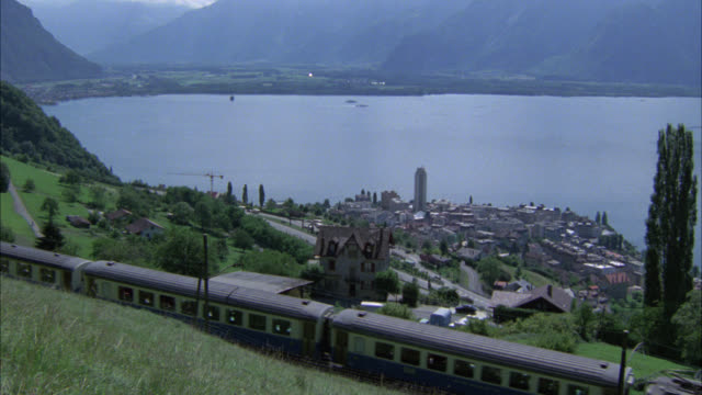 pan left to right of passenger train on railroad tracks traveling through countryside. grape vineyards. city or town on shore of lake. match  r804-1 through r804-3 and r804-7. mountains, alps. - switzerland stock videos & royalty-free footage