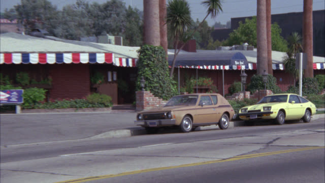 zoom in on brick building with red, white and blue decoration around roof. could be french restaurant (maison gerard). city street with cars driving in fg. palm trees. match r 803-04 through r803-05. - 1976 stock videos and b-roll footage
