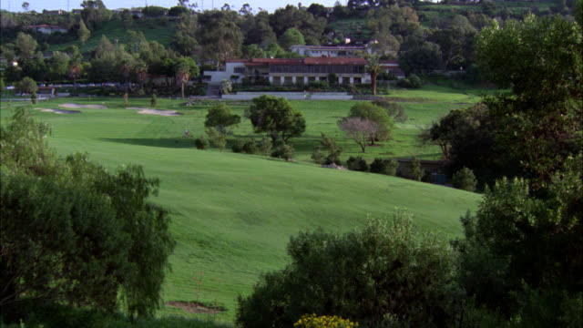 zoom in from golf course to clubhouse. could be resort or country club. green grass, trees. upper class. could be for vacation. - clubhouse stock videos & royalty-free footage