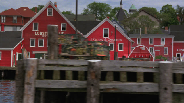 pan right to left moving pov from water of coastal town or fishing village. docks and piers. sea food restaurants. ship. could be cape cod. fishing boats. could be harbor. - eastern usa stock videos and b-roll footage