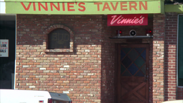 "pull back from close angle of neon sign and flashing police lights over brick building. neon sign reads ""vinnie's."" medium angle reveals awning reading ""vinnie's tavern."" could be police bar. - 1975 stock videos and b-roll footage"