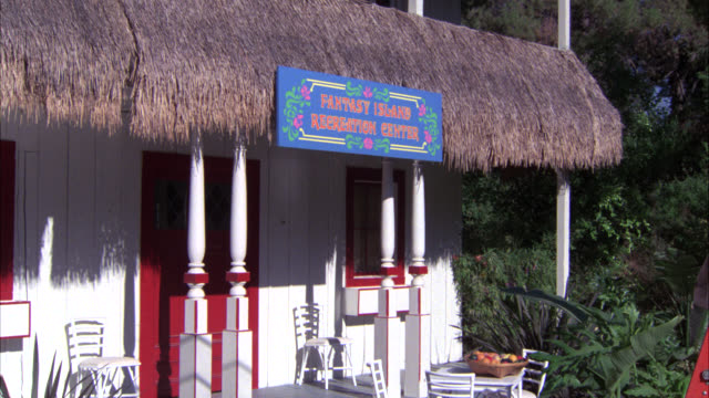 zoom in on sign for fantasy island recreation center. building with grass thatched roof. tropical. porch. - strohdach stock-videos und b-roll-filmmaterial