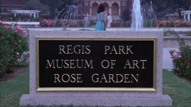 PULL BACK FROM SIGN FOR REGIS PARK MUSEUM OF ART AND ROSE GARDEN. ROSE BUSHES. FOUNTAINS. MUSEUM IN BG. ACTUALLY EXPOSITION PARK.