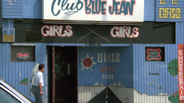 "vidéos et rushes de wide angle of ""club blue jean"" strip club. could be nightclub or adult entertainment. sign on building reads ""girls, girls, girls."" lower class urban area. - peep show"