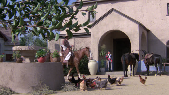 wide angle of spanish plaza. chickens hens in fg. horses in bg. horse drawn wagon. soldiers or army men or guards. spanish adobe style house. donkey, farmers, fountain. - the spanish donkey stock videos & royalty-free footage