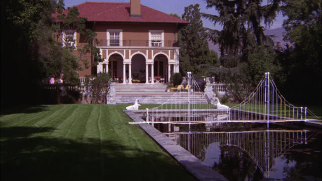 wide angle of chateau, mansion, estate, or manor with large lawn. elaborate reflecting pool with bridge. outdoor patio. could be mountain house. - 1981年点の映像素材/bロール