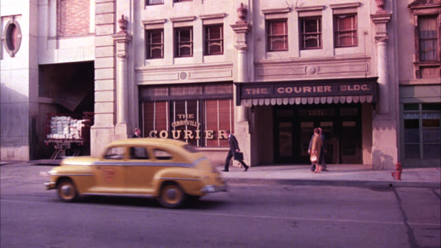 wide angle of city street with gibbsville courier newspaper office buildings. people or pedestrians walking on sidewalk. cars drive by. could be main street. sign for lintzie's ringside bar and pool hall. - pool hall stock videos and b-roll footage