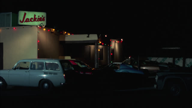 "stockvideo's en b-roll-footage met wide angle of sign for ""jackie's"" bar, night club, or restaurant. could be strip. suburbs or rural area. sherriff's pick up truck drives into parking lot and sherriff runs into building. christmas lights. - bar gebouw"