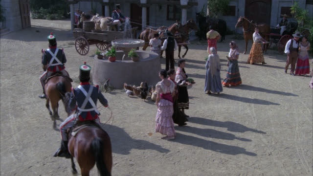 high angle down of spanish plaza. chickens hens in fg. horses in bg. horse drawn wagon. soldiers or army men or guards. spanish adobe style house. donkey, farmers, fountain. - the spanish donkey stock videos & royalty-free footage