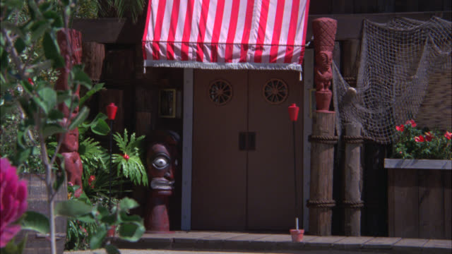 vídeos de stock, filmes e b-roll de pan down from fake or model lighthouse to entrance of tropical tiki bar or lounge. could be restaurant. couples walks in and out of building. tiki torches. striped awning. fishing net over window. tropical. - tocha tiki
