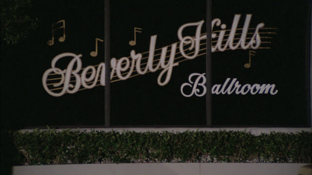 pull back from sign beverly hills ballroom in window to establish building. yellow car parked in front of entrance door. man and woman exit. could be nightclub. upper class. - ビバリーヒルズ点の映像素材/bロール