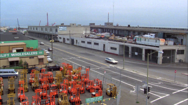 "vídeos de stock, filmes e b-roll de high angle down of china basin area in san francisco. waterfront buildings or industrial area with warehouses. ""wholesalers"" forklifts in fg . city streets leading to drawbridge in bg. cars speeding. could be car chase. barricaded gates onto open draw bri - drawbridge"