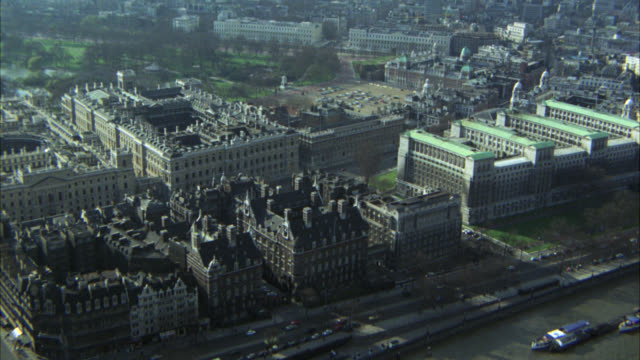 aerial of city of london. high rise office or apartment buidlings, parliament, big ben, parks, churches and river thames. city streets below with roundabouts or rotaries, cars and double decker buses. westminster palace. government buildings. - government building stock videos & royalty-free footage
