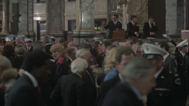 wide angle of lloyds of london. crowd of people. could be auction or stock market. people throw papers into air. med shot favoring rimbatten. - versteigerung stock-videos und b-roll-filmmaterial