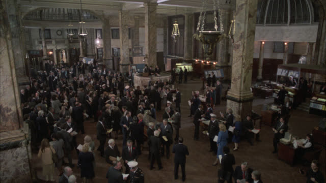wide angle of lloyds of london. crowd of people. could be auction or stock market. people throw papers into air. - auction stock videos & royalty-free footage