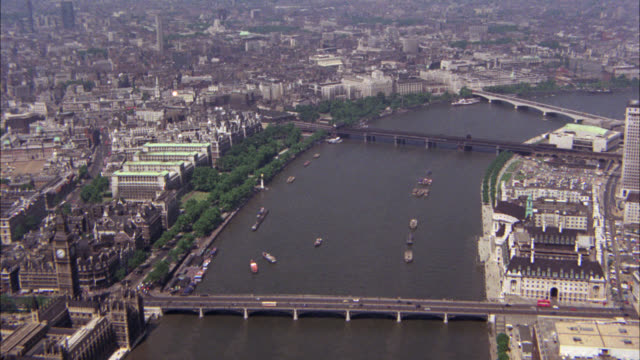 aerial of thames river in city of london. bridges. london high courthouse. could be church or cathedral. westminster palace or houses of parliament and big ben clock tower. multi-story and high rise office or apartment buildings. boats in water. matching - parliament building stock-videos und b-roll-filmmaterial