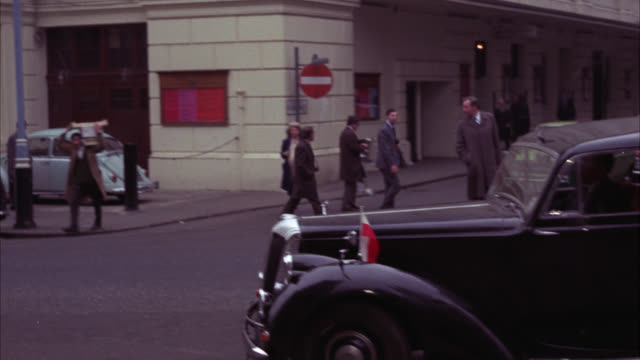 vídeos de stock, filmes e b-roll de pan left to right from sign for bow street magristrate court to black rolls royce waiting. could be diplomatic or government car. upper class. woman crosses street. - rolls royce