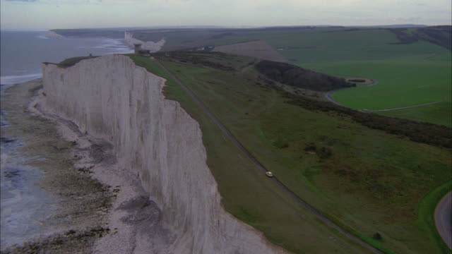 aerial pov of coastline of ocean along white cliffs of dover. see small white pick up truck or car drive along dirt road way or path on cliff above. shot in england mow. see green fields of countryside landscape with rolling green hills. - dover england stock videos and b-roll footage