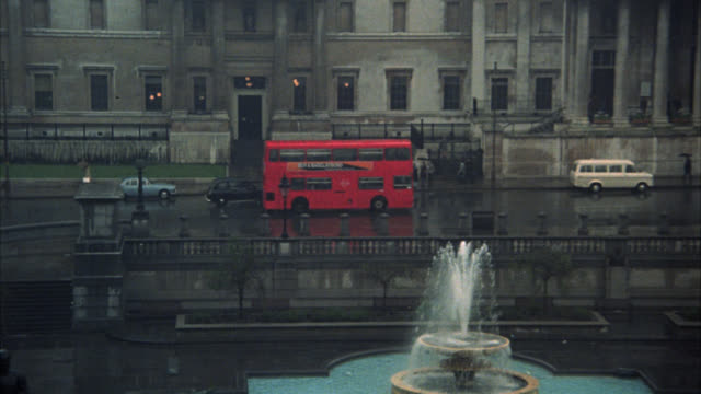 pan left to right across trafalgar square to window of multi-story office building. signs for charing cross and whitehall. could be government buildings. town squares. cars on city street. national gallery. art museum. fountains. - rain stock videos & royalty-free footage