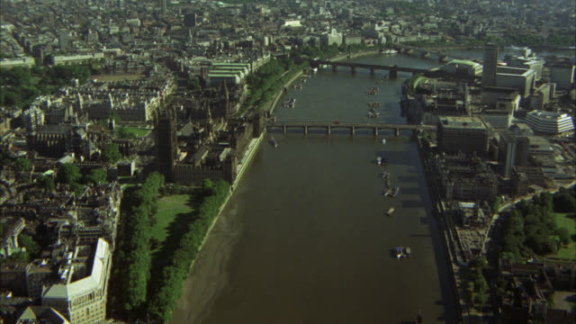 aerial of thames river in city of london. bridges. westminster palace or houses of parliament and big ben clock tower. multi-story and high rise office or apartment buildings. boats in water. matching r818-1 r818-7 r819-1 r819-4. - parliament building stock-videos und b-roll-filmmaterial