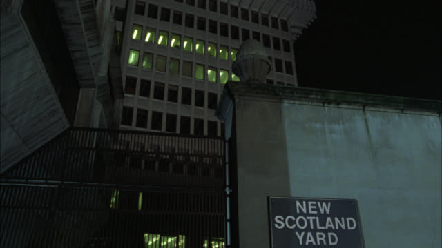 up angle of high rise office building. sign for new scotland yard. police department. iron gate. matching dx 1273-b  1271-c  1271-d 1331-f. - ニュースコットランドヤード点の映像素材/bロール