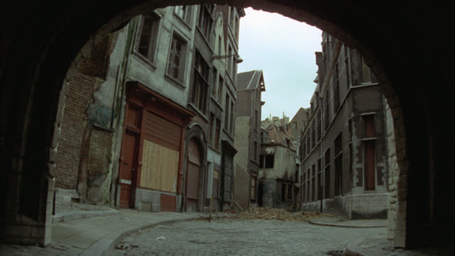 medium angle pov through arch of city street in lower class neighborhood. multi-story brick apartment buildings. alleys. could be in london. - bogen architektonisches detail stock-videos und b-roll-filmmaterial