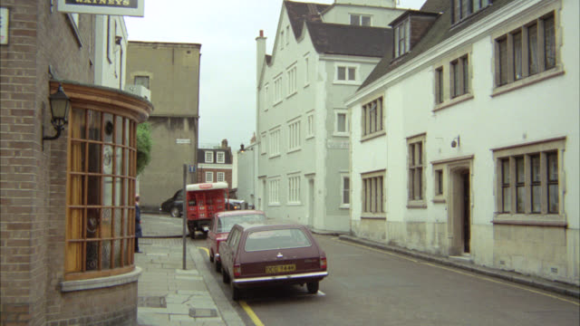 vídeos de stock e filmes b-roll de pan left to right of british street car enters from bg and turns right around corner. residential area. - 1974