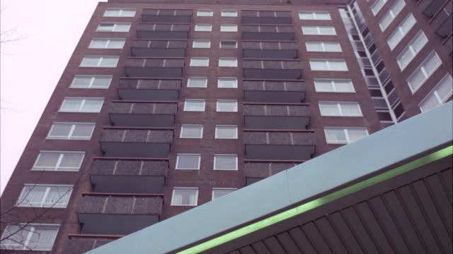 vidéos et rushes de pan down from up angle of multi-story middle class brick apartment building. each apartment has balcony. camera pans down to entrance of building. men conversing. - stéréotype de la classe moyenne