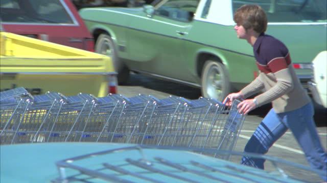 vídeos y material grabado en eventos de stock de pan right to left across supermarket parking lot as boy pushes shopping carts. cars. - carrito de la compra