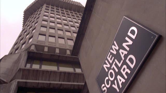 "up angle of multi-story non descript building and sign reading ""new scotland yard."" police headquarters. - ニュースコットランドヤード点の映像素材/bロール"
