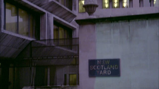 """pan up from city street and sign in front of building reading """"new scotland yard"""" to multi-story building. could be police headquarters or government building. series. - ニュースコットランドヤード点の映像素材/bロール"""