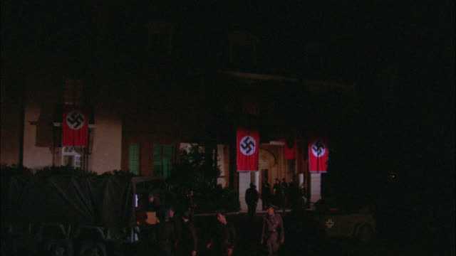 wide angle of german military headquarters with nazi flags flying. world war ii. army or military jeeps and soldier carrying red cross medical supplies into building. black car drives away from headquarters. army trucks. - nazi swastika stock videos and b-roll footage