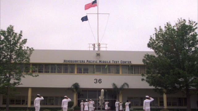 "vidéos et rushes de pull back from naval soldiers raising flags on mast atop of building reading ""headquarters pacific missile test center."" naval bases. men or soldiers stand at attention below building. - marine américaine"