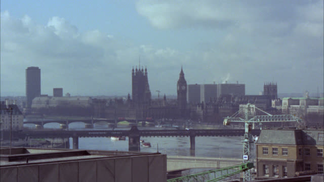 stockvideo's en b-roll-footage met pan left to right of london skyline. industrial area near thames river, factories with smokestacks. bridges. westminster. high rise and multi-story office and apartment buildings. stone buildings. cars on city streets below. government buildings. high cou - london england