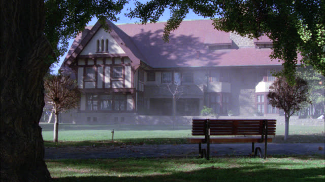 vidéos et rushes de wide angle of english, tudor house with half-timber framing. two story middle to upper class. could be mansion. very windy, dry leaves. park bench in fg. - demeure