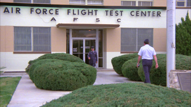 "vidéos et rushes de wide angle of air force soldiers in uniform on air force base. men salute superior officer. camera pans to sign above building reading ""air force flight test center."" could be cadets. - élève officier"