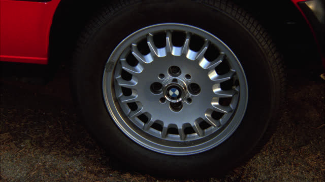 close angle on bmw wheel, tire, hubcap of a red car. car speeds off r-l. - bmw stock videos & royalty-free footage