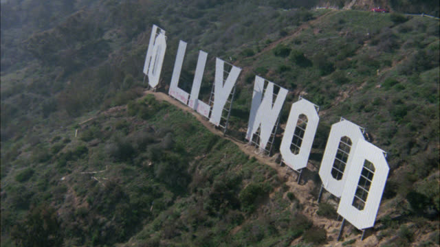 aerial over the hollywood sign in the hollywood hills. landmark. few people crouched behind the sign. mountains. - 1984 stock videos & royalty-free footage