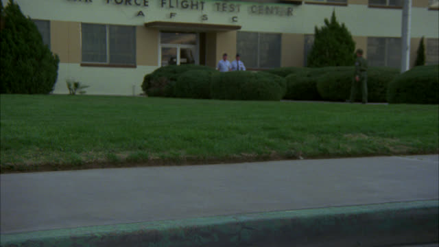 "vidéos et rushes de medium angle of sidewalk or curb outside of ""air force flight test center."" soldiers and cadets in uniforms walk around. car with license plate ""wings commander"" pulls up and officer exits. could be military police. series. - élève officier"