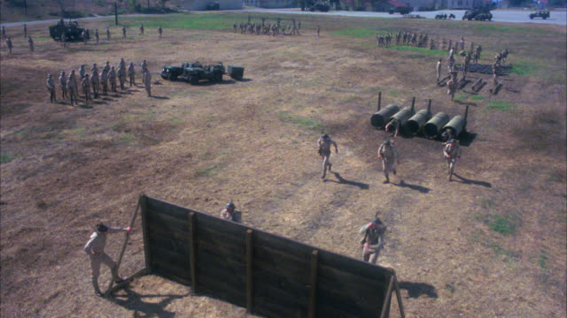 high angle down of military or army training drill course. soldiers in uniforms and officer. dirt field. wall to climb over, tunnels, and other obstacles. - hindernisparcours stock-videos und b-roll-filmmaterial