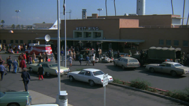 pan left to right from man and two women running from car in parking lot toward west wing of airport terminal. crowd of people running in panic toward entrance. news van. could be evacuation from natural disaster. emergency. - 1978 stock videos and b-roll footage