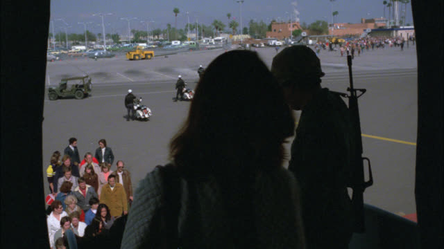 WIDE ANGLE POV FROM INSIDE THE CABIN OF A PLANE OR COMMERCIAL AIRLINER. SEE ARMED MILITARY GUARD STANDING AT THE DOORWAY WATCHING THE PEOPLE OR PASSENGERS BOARD. MOTORCYCLE POLICE OFFICERS ON THE TARMAC IN THE BG. PALM TREES. MULTIPLE NEG CUTS. SUDDENLY P