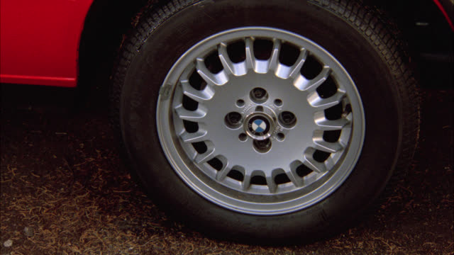 close angle of wheel, tire, hubcap on red bmw. see persons leg get into car then car off r-l fast. skid marks. - bmw stock videos & royalty-free footage