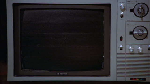 CLOSE ANGLE OF AN OLD 1970'S TELEVISION SET WITH KNOBS AND DIALS. TV IS OFF. NO PICTURE.