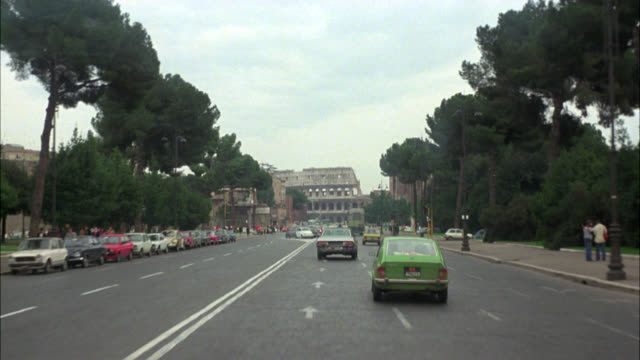 wide angle driving pov straight forward of european city street. multi-story brick office or apartment buildings. cobblestone street. ancient ruins. columns or pillars. coliseum or amphitheater. roman arch of constantine. - colosseo video stock e b–roll