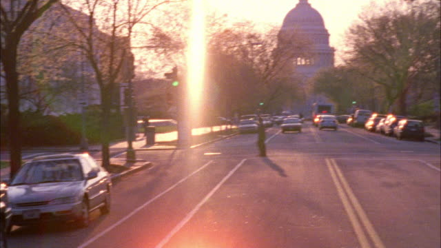 vídeos de stock e filmes b-roll de pan left to right from a woman walking dogs along residential street to end of street with capitol building in horizon. domed buildings. government buildings. cars driving on street. - 2002