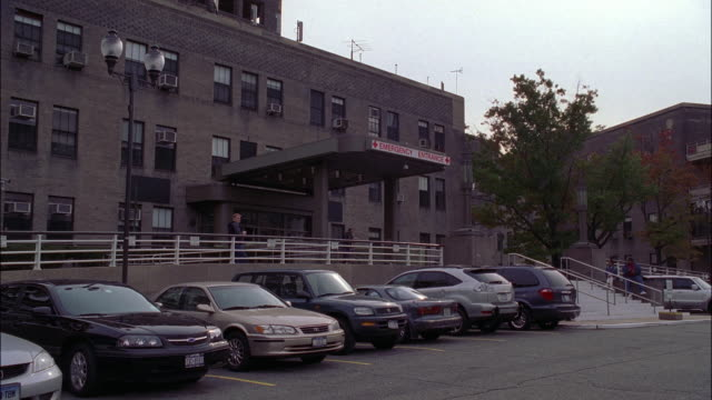 "wide angle of old brick hospital, emergency room entrance, parking lot, cars and jeeps parked. men, women enter, exit building. matching dx/nx 2253-032 to 2253-046.<p><a href=""https://www.sonypicturesstockfootage.com/footage?kid=4379"">for day-night matchi - parkfläche stock-videos und b-roll-filmmaterial"