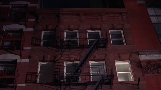 medium angle of multi-story brick building with fire escape. alleys, windows. apartment buildings. middle class. - fire escape stock videos and b-roll footage